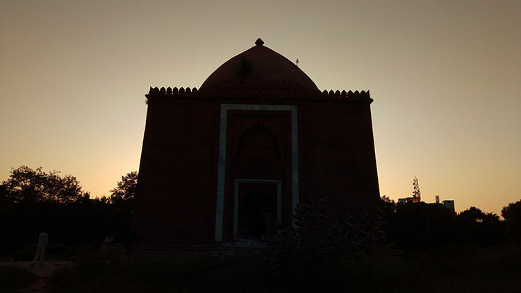 The sun sets over the Lal Gumbad